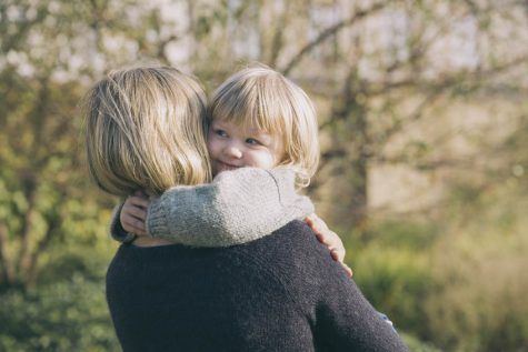 Little girl smiling cuddling her mother